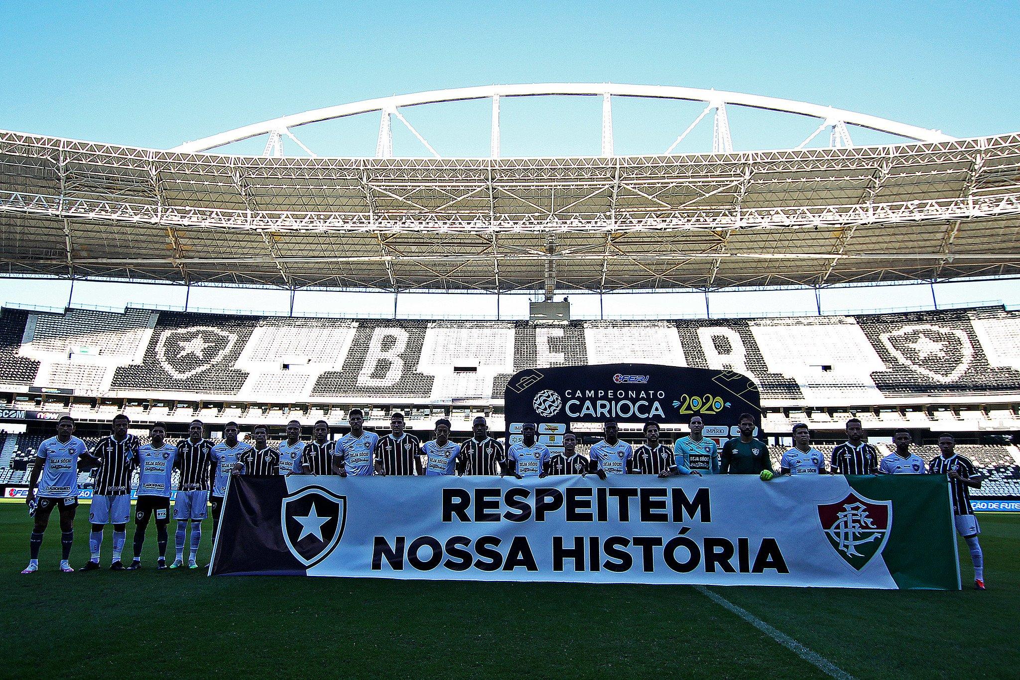 """Jogadores de Botafogo e Fluminense com a faixa de protesto """"Respeitem nossa história"""""""